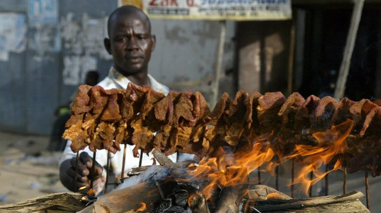 A man arranges sticks of meat on a mud platform for roasting in the ancient city of Kano 19 April, 2007. Roasted meat on sticks popularly known as 'Suya' is a common delicacy in northern Nigeria. AFP PHOTO PIUS UTOMI EKPEI