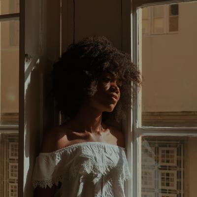 woman leaning on a window, sad