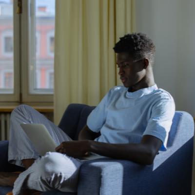 Black boy using laptop on a chair